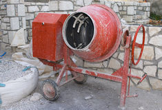 Cement mixer. A small, red cement mixer on a building site
