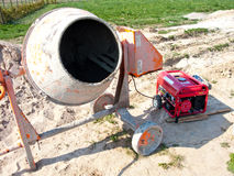 Cement mixer. Closeup of a small, portable cement mixer and electric generator on a construction site stock image