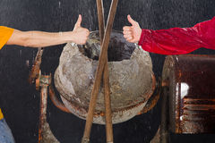Two workers show Thumbs up in front of cement mixer. Cement mixer at the end of the day Stock Image