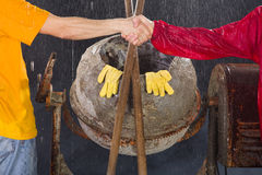 Two workers shake their hands in front of cement mixer. Stock Photo