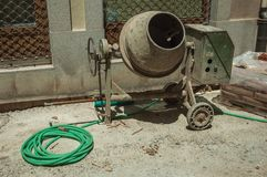 Cement mixer with hose and cement bags in a construction site stock photos