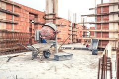 Cement mixer machine at construction site, tools, wheelbarrow, sand and bricks at house building. Royalty Free Stock Image