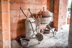 Cement mixer machine, wheel barrow and other construction site tools after working hours Royalty Free Stock Photos