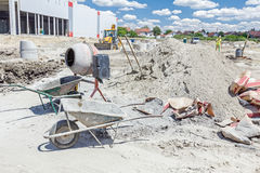 Cement mixer machine and wheelbarrow at building site Stock Images