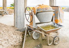 Cement mixer. Old Cement mixer machine with sand truck stop beside at a construction site Royalty Free Stock Images