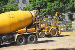 Cement mixer truck and excavator. Vehicle at the construction site Royalty Free Stock Photos