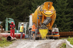 Cement mixer truck. Falcade, Belluno, Italy - August 21, 2015: Cement mixer truck works at building site under construction the new modern cabin lift in the ski stock photos