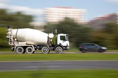 Cement mixer truck motion. Panning image of cement mixer truck in intentional blurred motion on a street stock images