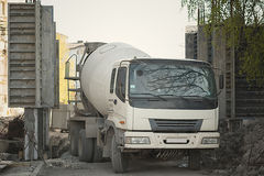 Cement mixer truck parked. In front of a new building under construction with scaffolding royalty free stock images