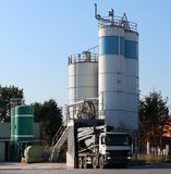 A cement mixer truck is supplied to a concrete silo in a batching plant.  stock photography