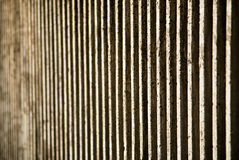Cement Patterned Wall. A cement retaining wall with a pattern of vertical lines in the bright sunlight disappearing into perspective Stock Image