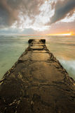 Cement pier extends out to the horizon during a cloudy sunset Stock Image