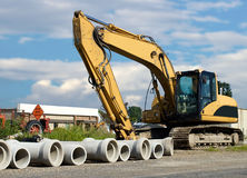 Cement pipes with backhoe Royalty Free Stock Photography
