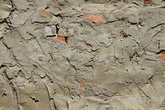 Cement plastering layer on brick wall. Cement uneven rough plastering layer on unfinished brick wall of construction site Royalty Free Stock Photo