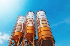 Cement silos of Cement batching plant factory. Against afternoon sun with clear blue sky royalty free stock images