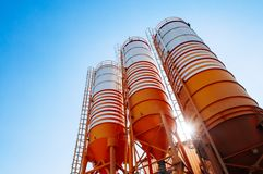 Cement silos of Cement batching plant factory. Against afternoon sun with clear blue sky royalty free stock photos