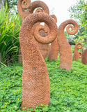 Cement statue. Orange cement statue fern in garden with grass Royalty Free Stock Image