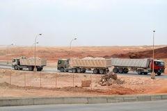 Cement Transportation. Heavy long vehicles transportaing cement stones in raw stock photos