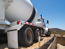 Cement Truck on Excavation Site - Horizontal. A cement truck is parked outside in a desert area.  It is next to an excavation site.  Horizontally framed shot Royalty Free Stock Photo