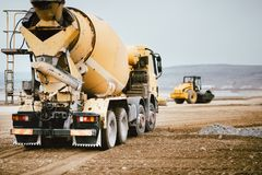 Industrial Cement truck on highway construction site. Heavy duty machinery at work on construction site. Cement truck on highway construction site. Heavy duty stock photos