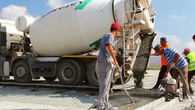 Cement truck pouring cement into a runway construction stock footage
