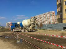 Cement truck stands on construction site with tape fence near multi-storey building under construction. Under boundless blue sky on sunny day stock photo
