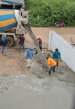 A cement truck and worker are pouring cement to new floor. NAKHON RATCHASIMA -JULY 6 : A cement truck and worker are pouring cement to new floor at construction Royalty Free Stock Image