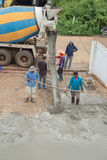 A cement truck and worker are pouring cement to new floor. NAKHON RATCHASIMA -JULY 6 : A cement truck and worker are pouring cement to new floor at construction Stock Photos