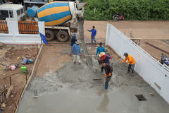 A cement truck and worker are pouring cement to new floor. NAKHON RATCHASIMA -JULY 6 : A cement truck and worker are pouring cement to new floor at construction Stock Photo