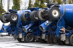 Cement Trucks. A row of blue cement trucks with their back wheels up Stock Photo