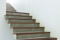 Cement and wood staircase on white mortar wall Royalty Free Stock Photography