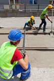 Cement workers. Construction team pouring concrete on a road with boots and protection gear Royalty Free Stock Image
