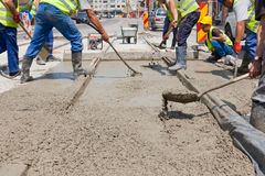 Cement workers. Construction team pouring concrete on a road with boots and protection gear Stock Image