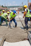 Cement workers. Construction team pouring concrete on a road with boots and protection gear Stock Images