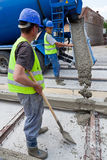 Cement workers. Construction team pouring concrete on a road with boots and protection gear Royalty Free Stock Photos
