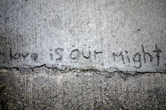 Cement Writing Love. Love is our might scrawled in concrete royalty free stock images
