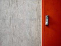 Cementbetongväggtextur med den moderna röda dörren Royaltyfria Bilder
