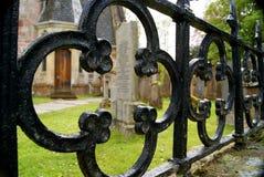 Cementerio con la lápida mortuoria a través de la verja Imagen de archivo libre de regalías
