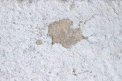 Cementi la parete con le crepe ed allenti i pezzi di struttura sporca della pittura immagine stock