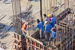Cemento de colada del trabajador que vierte en fundaciones y encofrado de los pilares en el área del edificio en emplazamiento de imagenes de archivo