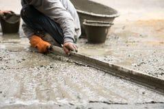 Cemento de enyesado de trabajo con la paleta para el nuevo piso de la estructura para reno fotos de archivo libres de regalías