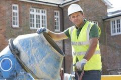 Cemento mescolantesi dell'operaio di costruzione Fotografia Stock