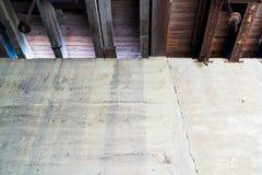 Cemento nudo sotto la parete con le capriate di legno fotografia stock