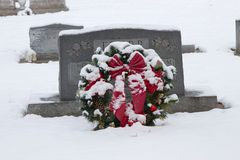 A Cemetary Christmas Wreath. A Christmas wreath next to a headstone during the holiday season royalty free stock photo