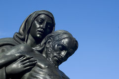 Cemetery 00. Mary and jesus in bronze against blue sky stock image