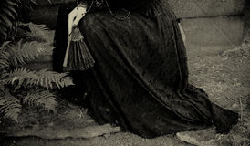 At the cemetery. Young woman in long black skirt crying at the cemetery Stock Photo