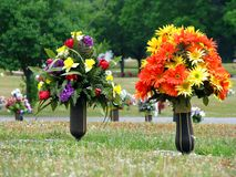 Cemetery. Colorful silk flower vases in summer cemetery Stock Image