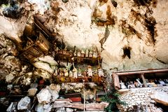 The cemetery with coffins placed in cave and balconies with wooden statues tau tau. Old burial site in Londa, Tanaja, Indonesia. Old torajan burial site in Londa Stock Images