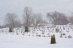 Cemetery covered in snow in Gatineau, Quebec. Cemetery covered in big layer of snow on a cold grey winter day in Gatineau, Quebec, Canada stock photo