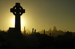 Cemetery cross. Dusk at cemetery, black and yellow tonality, cross in foreground Stock Photo
